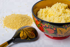 Millet porridge in a beautiful bowl with scattered millet. On a white tablecloth Stock Images