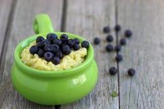 Millet porridge. Bowl with fresh berries . Shallow DOF royalty free stock photos