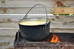 Millet porridge in a pot on the grill with fire, on the wooden fence background stock photos