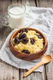 Millet porridge with prunes. Millet milk porridge with plums on a wooden background. Russian kitchen stock photos