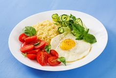 Millet porridge and tomato, cucumber salad and fried eggs. Healthy breakfast. Dietary menu. Millet porridge and tomato, cucumber salad and fried eggs royalty free stock photo