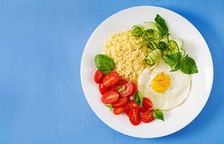 Millet porridge and tomato, cucumber salad and fried eggs. Healthy breakfast. Dietary menu. Millet porridge and tomato, cucumber salad and fried eggs. Top view stock photography
