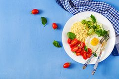 Millet porridge and tomato, cucumber salad and fried eggs. Healthy breakfast. Dietary menu. Millet porridge and tomato, cucumber salad and fried eggs. Top view stock images