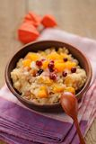 Millet porrige with pumpkin in clay bowl with wooden spoon. On wooden background Royalty Free Stock Images