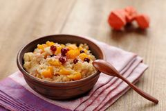 Millet porrige with pumpkin in clay bowl with wooden spoon. On wooden background Stock Photography
