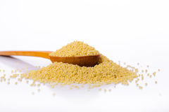 Millet in a wooden spoon Stock Photos