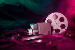 8 Millimeter-Filmkamera mit einer Spule des Filmes im grünen und purpurroten Rauche Stockfotografie