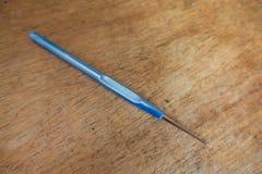 1 25 Millimeter-Häkelnadel mit blauem Griff auf Holz Lizenzfreie Stockfotografie