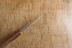 1 5 Millimeter-Häkelnadel mit braunem Griff auf Holz Stockfotos