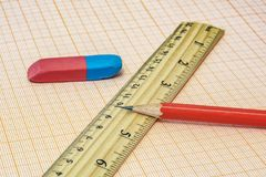 On the millimeter paper lie a ruler, an eraser and a simple pencil close-up. On the millimeter paper lie an eraser with a ruler and a simple pencil close-up royalty free stock photos