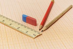 On the millimeter paper are two simple pencils, an eraser and a. On a millimeter paper there is a wooden ruler, an eraser and two simple pencils stock photo