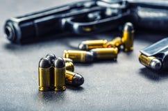 9 Millimeter-Pistolengewehr und -kugeln auf dem Tisch gestreut Stockfotos