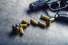 9 Millimeter-Pistolengewehr und -kugeln auf dem Tisch gestreut Stockfotografie
