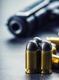 9 Millimeter-Pistolengewehr und -kugeln auf dem Tisch gestreut Stockfoto
