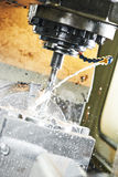 Milling the metal blank with coolant Stock Images