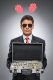 Millionär. Überzeugter Mann in der formellen Kleidung, die ein Koffer ful hält stockfotografie