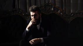 Million?r in der eleganten Klage sitzt auf luxuri?sem Sofa Reifer Mann mit ernstem Gesicht im klassischen Innenraum vertrauen stock video