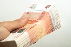 Male hand holds a thick stack of cash money. Million Russian rubles. The concept of rich, wealth, profits, business and finance. Million Russian rubles. The royalty free stock photos