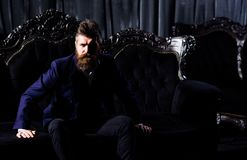 Millionaire in elegant suit sits on luxurious sofa. Angry boss, business, rich, power, wealth, money concept. Bearded man with angry, serious face in classic Stock Photo