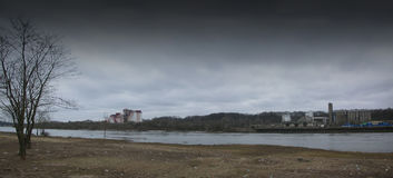 Mills are located on the river bank. Depressive panorama. Industrial landscape Royalty Free Stock Images