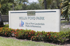 Mills Pond Park Entrance Sign. Fort Lauderdale, FL, USA - May 16, 2017: Large entry signage with red flowers at the entrance to Mills Pond Park. Front sign in Royalty Free Stock Photo