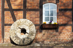 Millstone in front of half-timbered house Royalty Free Stock Photography