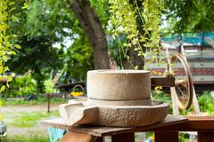 Millstone placed on the wooden porch. stock image