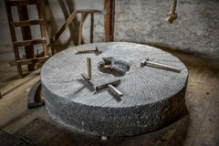 Millstone with tools Royalty Free Stock Image