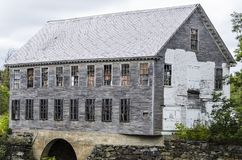 Shell of old spool factory standing on Sebec River Stock Images