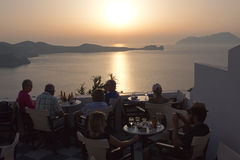 Milos - Greek cafe at dusk, view from Plaka, Cyclades islands. Milos, Greece - September 17, 2016:people at sunset over the Milos bay in the Plaka open-air cafe royalty free stock photos