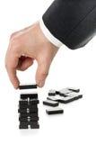 Milstolpe- eller framstegbegrepp - släp för dominobricka för byggnad för affärsman arkivbild