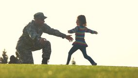 Miltary man return from the army meeting his daughter. Soldier standing on one knee with embracing arms in the air stock footage