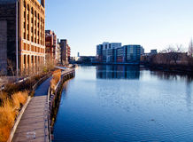 The Milwaukee River. Reflections of buildings and the riverwalk pedestrian boardwalk, along the Milwaukee River in the Historic Third Ward of Milwaukee Royalty Free Stock Image