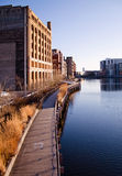 The Milwaukee River. Reflections of buildings and the riverwalk pedestrian boardwalk, along the Milwaukee River in the Historic Third Ward of Milwaukee Stock Photography