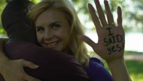 Mim sim frase triste escrita na mão da jovem mulher, menina que abraça o homem afro-americano video estoque