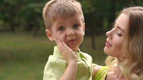 Mime a abrazar a su niño durante paseo en el parque Retrato de la madre y del hijo almacen de video