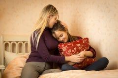 Mime a abrazar y a solacing a la hija adolescente en el dormitorio Imagenes de archivo