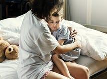 Mime al abrazo y a consolar al niño pequeño de la pesadilla foto de archivo