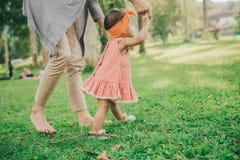 Mime al bebé de enseñanza para caminar en el parque Imagenes de archivo