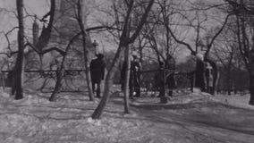 Mime al control del pequeño hijo de las manos en el sombrero de piel, capa Caminata en parque del invierno Lengua de la demostrac almacen de video