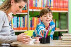 Mime al libro de lectura de la biblioteca a su hijo imágenes de archivo libres de regalías