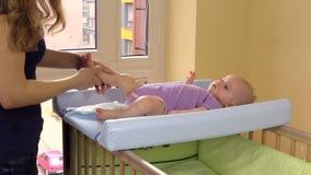 Mime al masaje y ejercite sus pequeñas piernas de la hija del bebé en cama almacen de metraje de vídeo