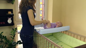 Mime al masaje y ejercite sus pequeñas piernas del bebé en su cama almacen de video