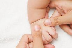 Mime al masaje y a la mano del reflexology de su bebé fotografía de archivo libre de regalías