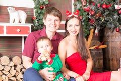 Mime al padre y al hijo que se sientan cerca de árbol de Navidad con los regalos Fotos de archivo