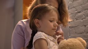Mime al pelo del trenzado de su pequeña hija y de besarla, sentándose en sitio moderno de vida, concepto de familia dentro almacen de metraje de vídeo