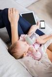 Mime a alimentar a su bebé con la botella de leche en sala de estar Fotos de archivo