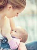 Mime a alimentar a su bebé en naturaleza al aire libre en el parque Fotos de archivo libres de regalías