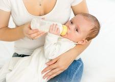 Mime a alimentar sus 3 meses del bebé de la botella Imagen de archivo libre de regalías
