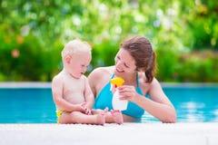 Mime a aplicar la pantalla de sol en bebé en piscina Imágenes de archivo libres de regalías